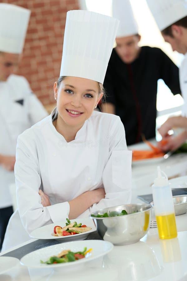 Studentflicka i matlagninggrupp arkivbild