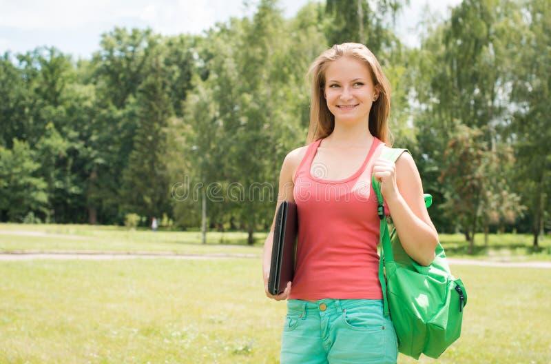 Studentflicka med bärbar dator- och skolapåsen utomhus Parkerar den unga kvinnan för högskolan eller för universitetsstudenten i  royaltyfri bild