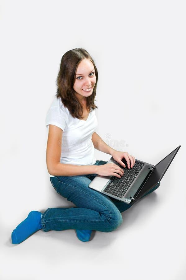 Studentflicka med bärbar datordatoren på grå bakgrund arkivbild