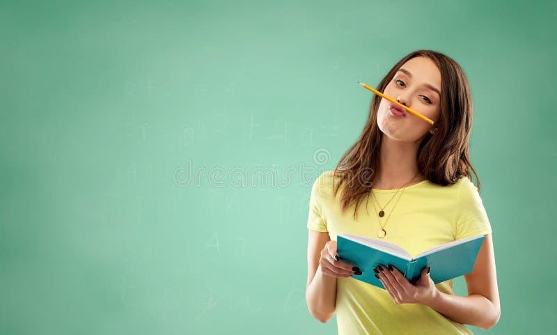 Studentflicka med boken och blyertspennan över gräsplan arkivbilder