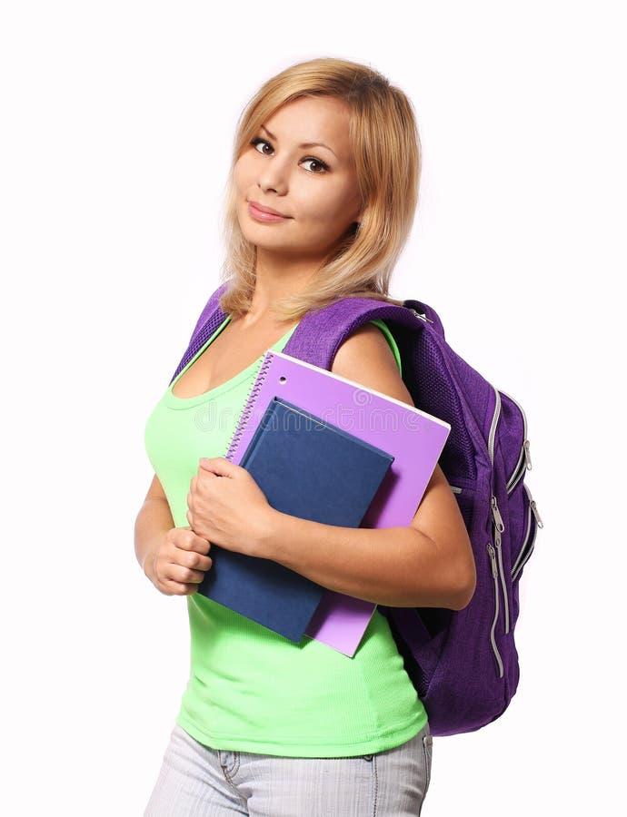 Studentflicka med den isolerade ryggsäcken och böcker arkivfoton