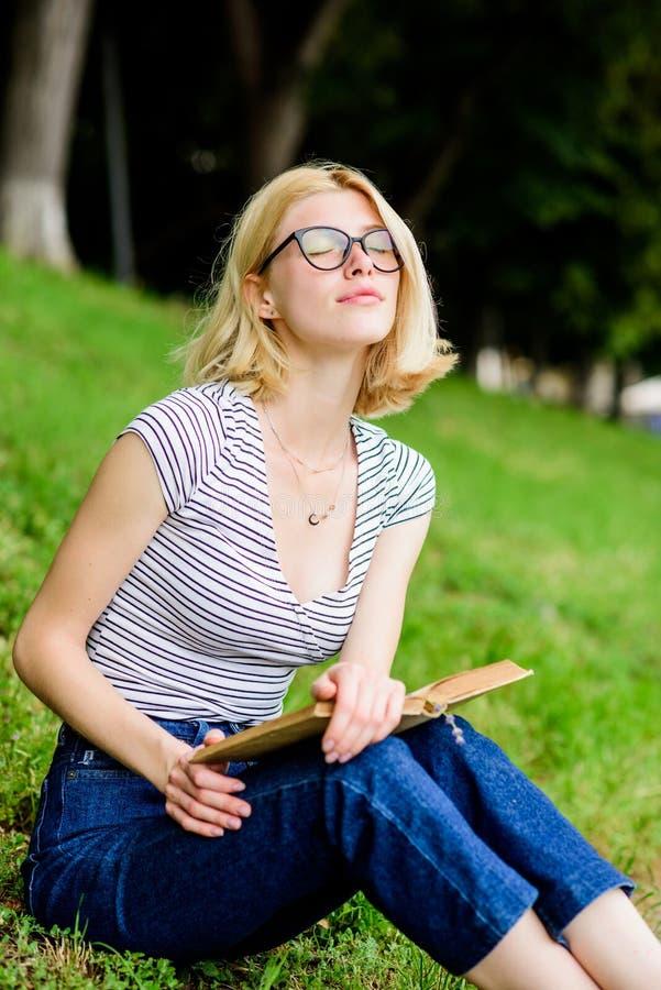 Studentflicka med den utomhus- boken kvinnan parkerar in läseboken intressant ber?ttelse Koppla av och få ny information läsning  arkivfoto