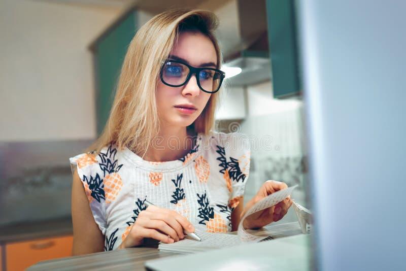Studentflicka med exponeringsglas som gör läxa i en pappers- notepad royaltyfria foton