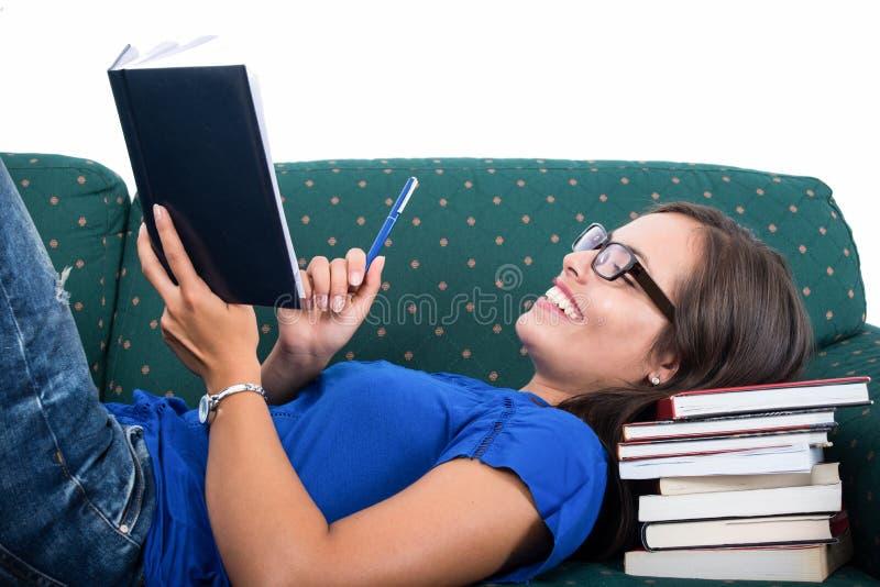 Studentflicka som läggas på soffan som ler den hållande anteckningsboken arkivfoton