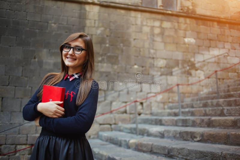 Studentflicka som nästan rymmer den röda boken hennes bröstkorganseende på universitetsområde arkivfoton