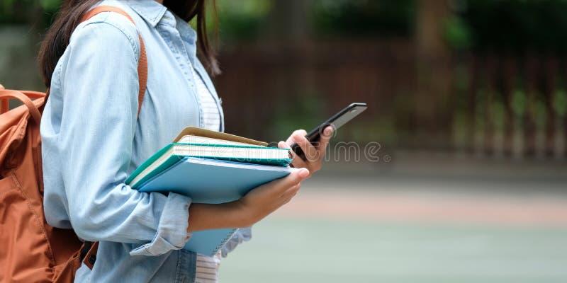 Studentflicka som rymmer böcker och smartphonen, medan gå i schoo royaltyfri foto