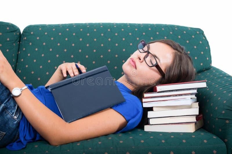 Studentflicka som sover på den hållande anteckningsboken för soffa arkivfoto