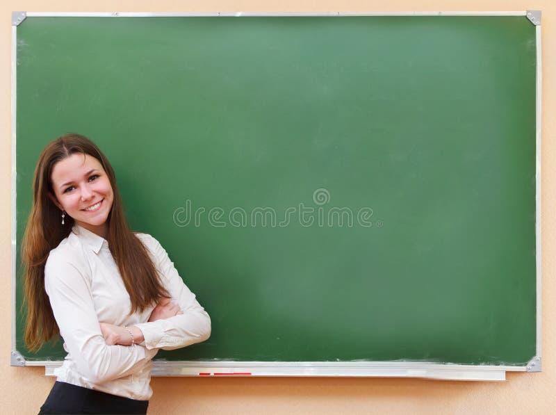 Studentflicka som står den near svart tavla i klassrumet arkivbilder