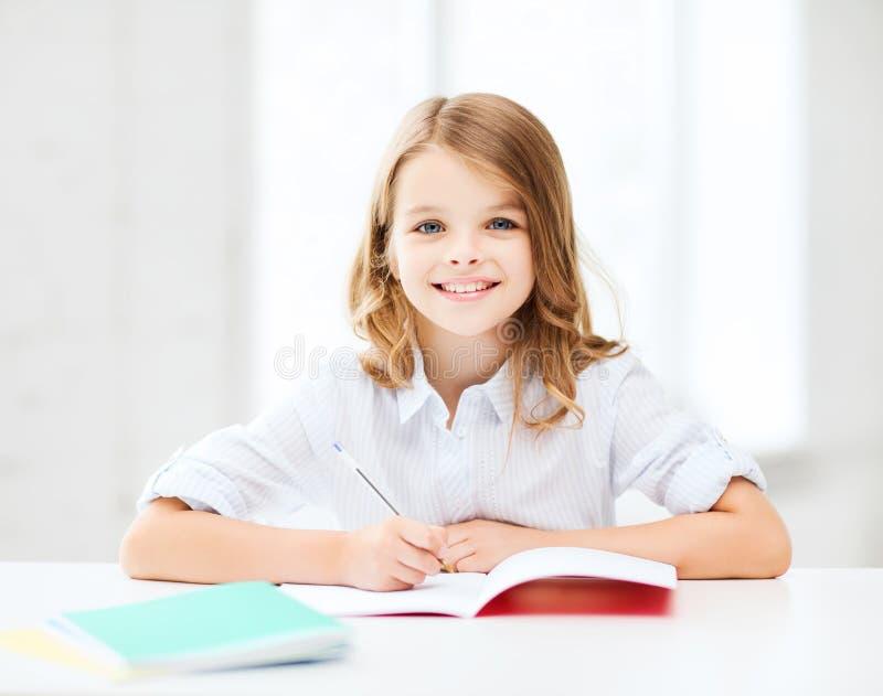 Studentflicka som studerar på skolan royaltyfri fotografi
