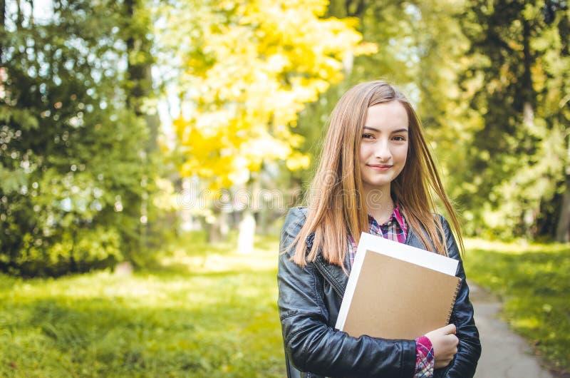 Studentflicka som utomhus tillbaka går till skolan och att le fotografering för bildbyråer