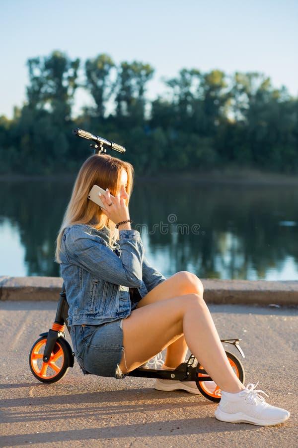 Studentflickasammanträde på en sparkcykel i natur royaltyfri foto