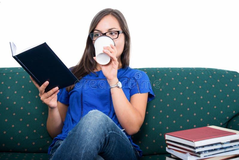 Studentflickasammanträde på soffaläsning som dricker kaffe arkivbilder