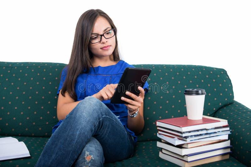 Studentflickasammanträde på soffan som smsar på minnestavlan royaltyfria bilder
