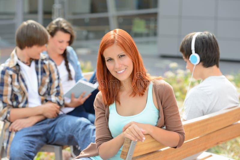 Studentflickasammanträde utanför universitetsområde med vänner royaltyfri bild