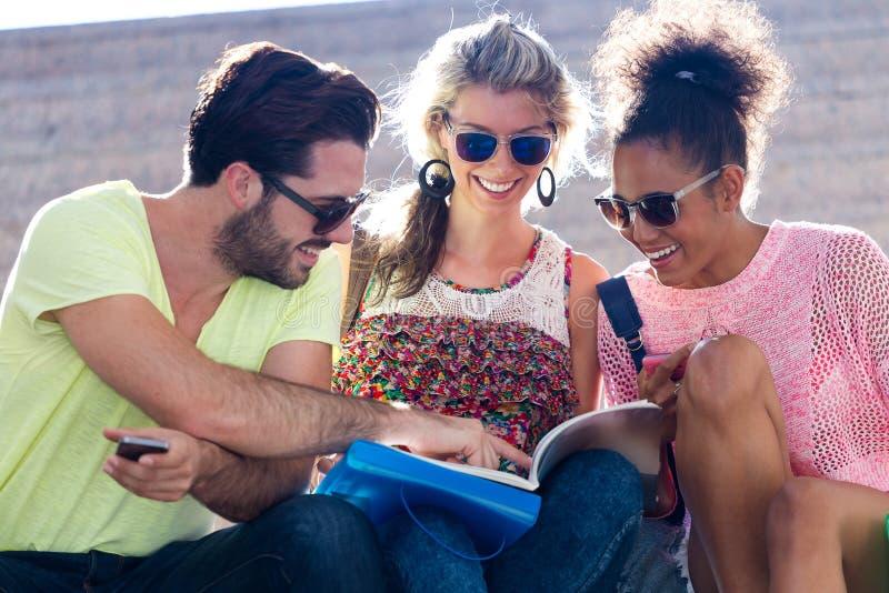 Studentgrupp som ser en bok i gatan arkivbilder