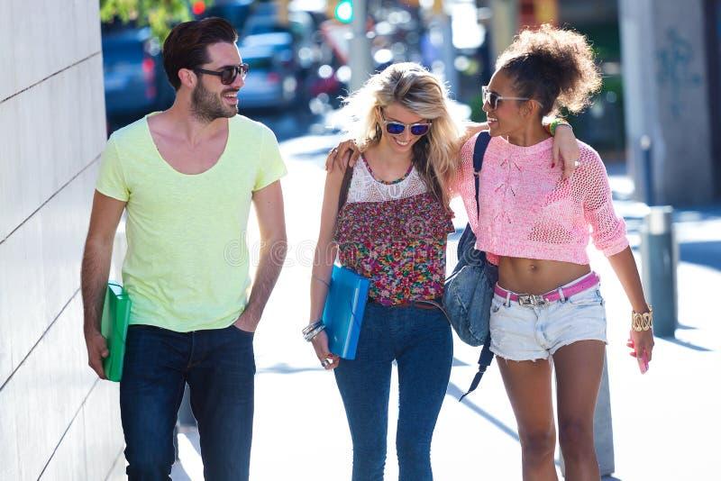 Studentgrupp som talar och skrattar i gatan arkivbilder