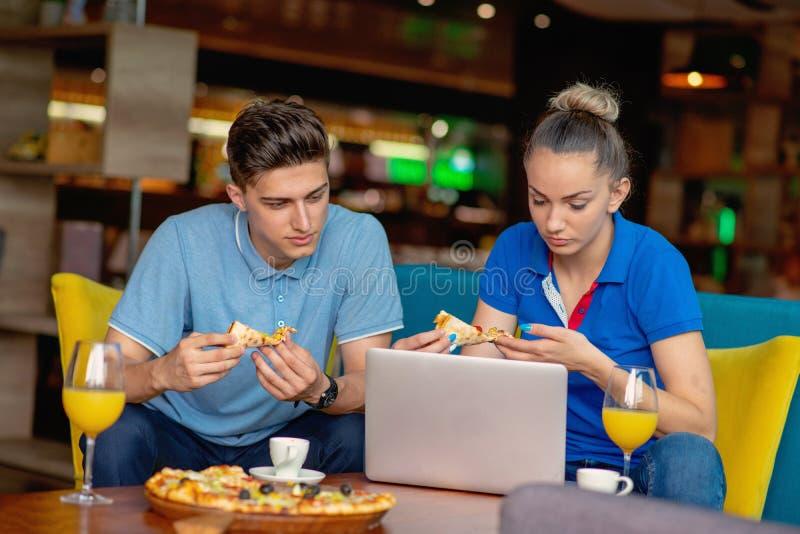 Studentgruppen som äter pizza, i avbrott av nästa studiegrupp för tid som tidigt har gyckel, och tycker om den italienska matskiv arkivbilder