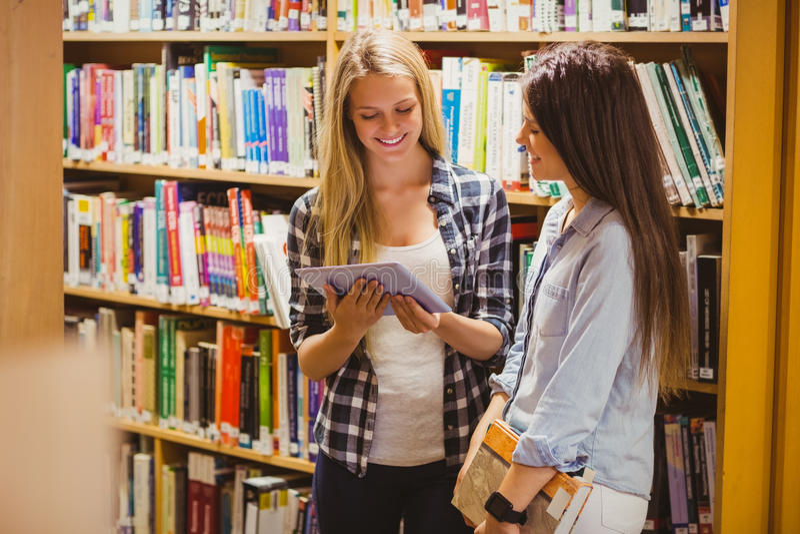 Studenti abbastanza giovani che collaborano con la compressa fotografie stock libere da diritti