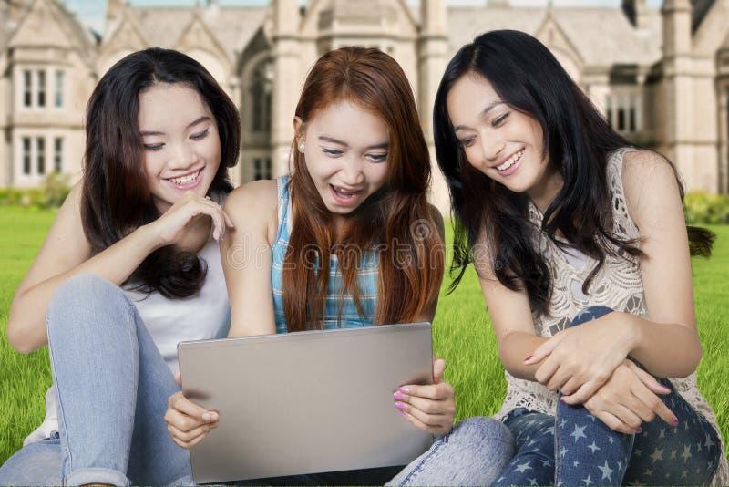 Studenti adolescenti con il computer portatile al cortile della scuola fotografia stock libera da diritti