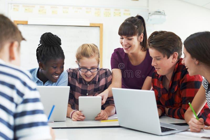 Studenti adolescenti con la classe di In l'IT dell'insegnante fotografia stock