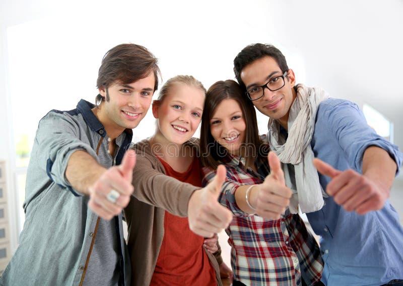Studenti allegri con i pollici su immagini stock