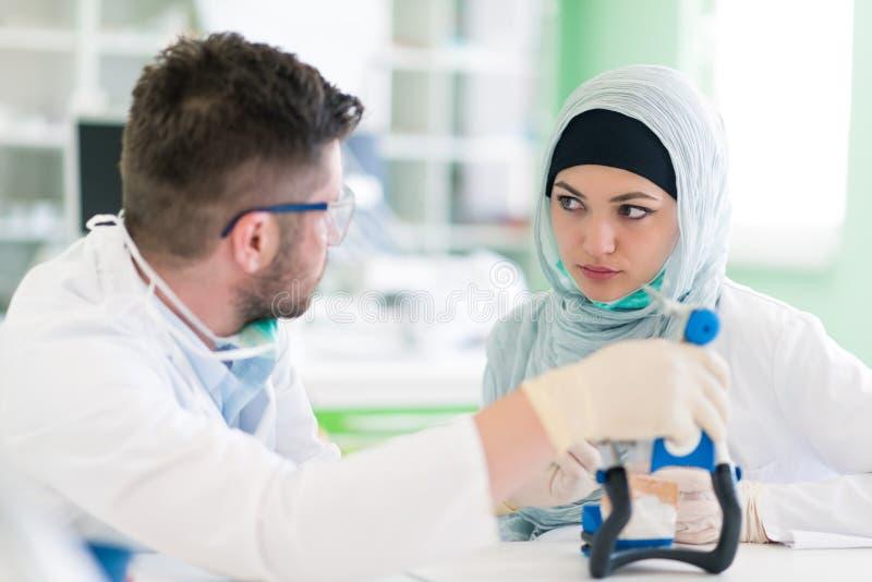 Studenti arabi con hijab mentre lavorando alla protesi dentaria, denti falsi fotografie stock libere da diritti