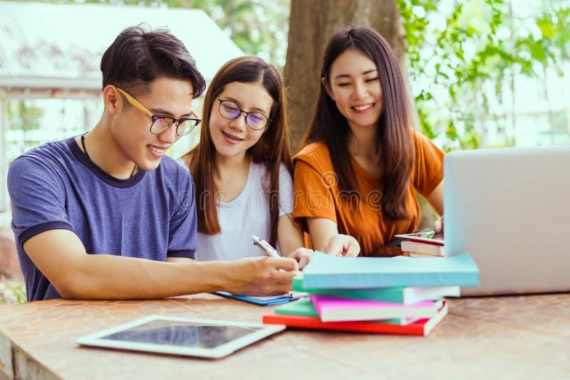 Studenti che aiutano amico a consultarsi, istitutore, lavoro di squadra immagini stock libere da diritti