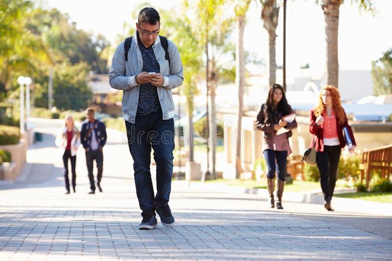 Studenti che camminano all'aperto sul campus universitario immagini stock libere da diritti