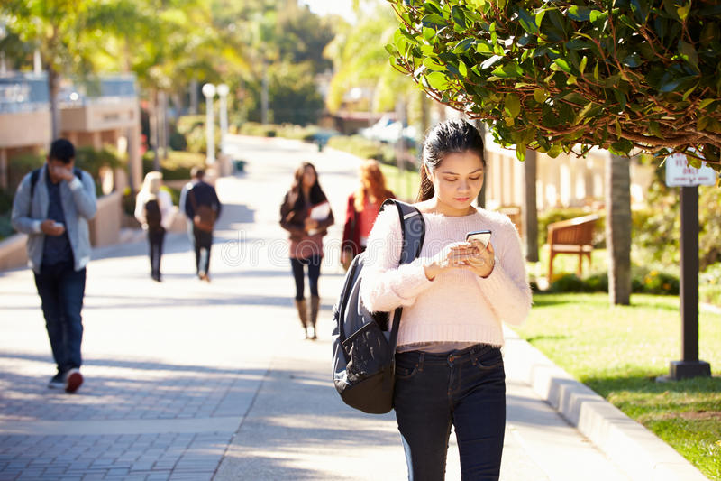Studenti che camminano all'aperto sul campus universitario immagini stock