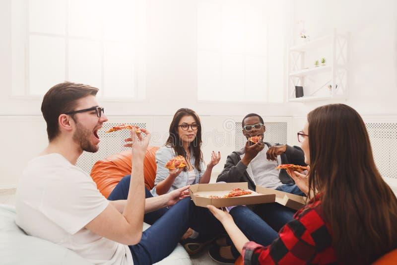 Studenti che dividono il partito della pizza a casa immagine stock