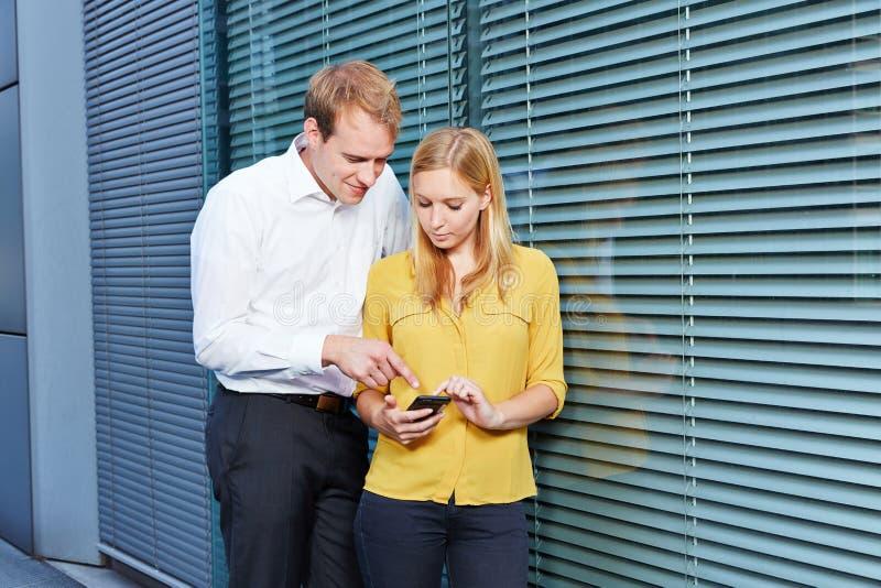 Studenti che esaminano sito Web sul loro smartphone fotografie stock