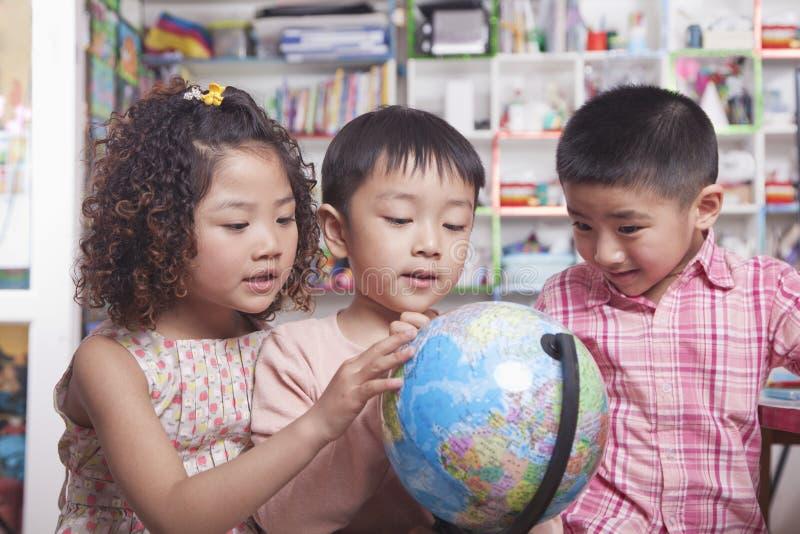 Studenti che esaminano un globo fotografie stock libere da diritti