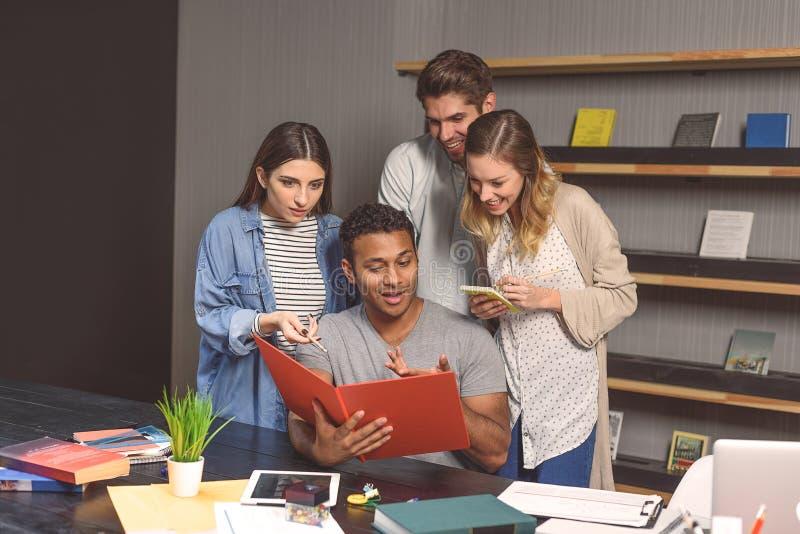 Studenti che fanno progetto del gruppo nella biblioteca della città universitaria fotografia stock libera da diritti