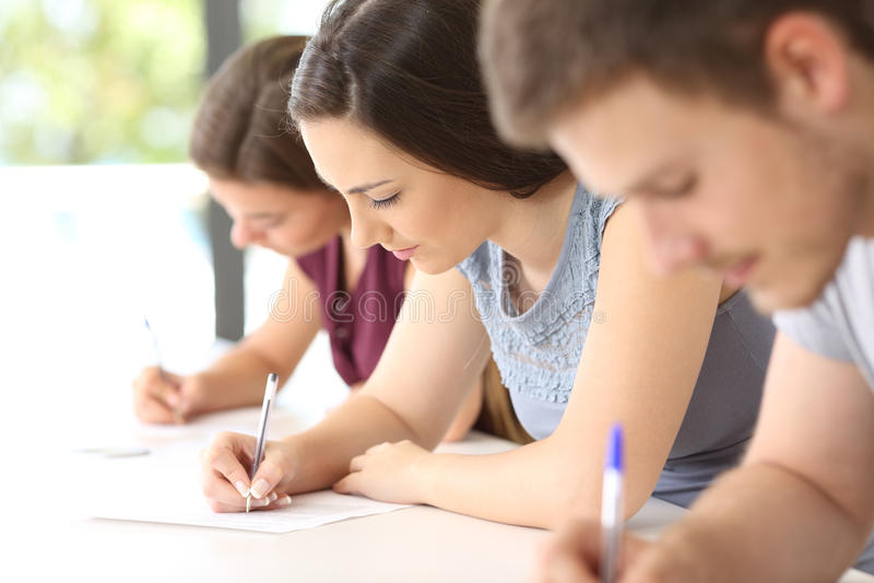 Studenti che fanno un esame in un'aula fotografia stock