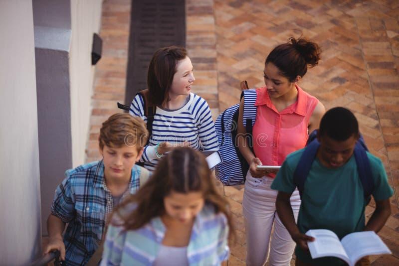 Studenti che giudicano i libri e compressa digitale che camminano attraverso la città universitaria della scuola immagine stock libera da diritti
