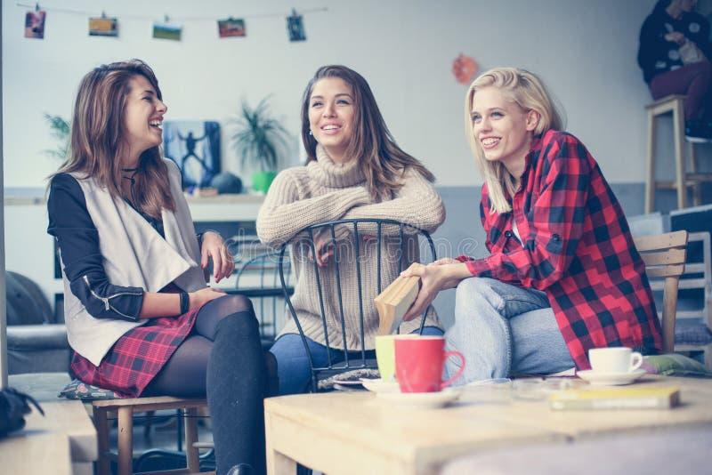 Studenti che imparano in un caffè Tre amici che hanno conversazione fotografie stock