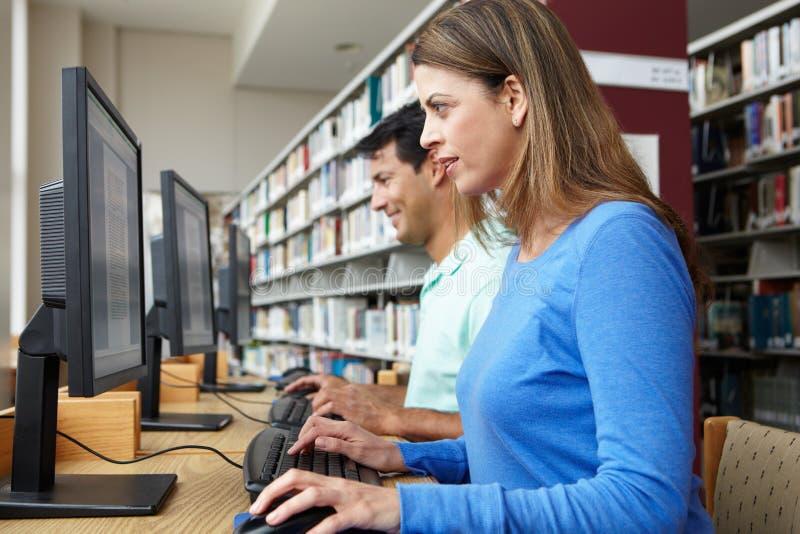 Studenti che lavorano ai computer in biblioteca fotografie stock