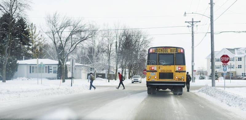 Studenti che scendono scuolabus durante l'inverno fotografia stock