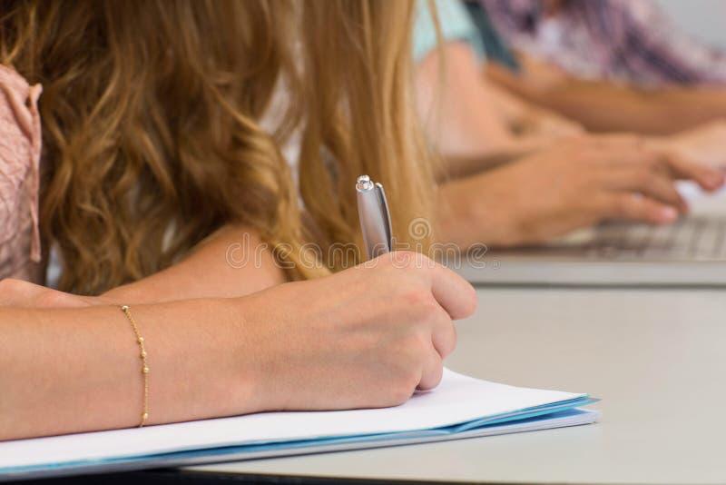 Studenti che scrivono le note nell'aula immagine stock