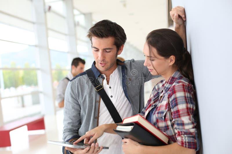 Studenti che stanno nel corridoio facendo uso della compressa immagini stock libere da diritti