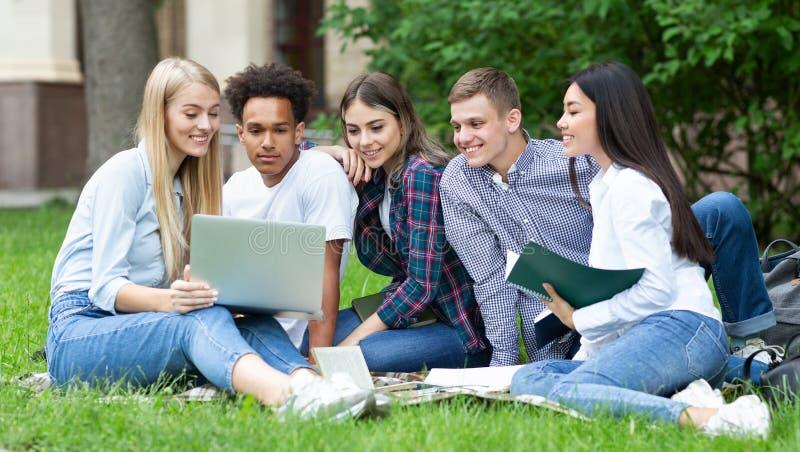 Studenti che studiano nell'aria aperta di progetto del gruppo nella città universitaria dell'istituto universitario fotografia stock libera da diritti