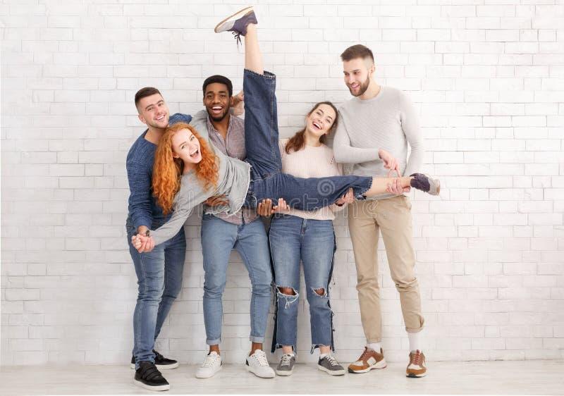 Studenti che tengono amico e che si divertono sopra il muro di mattoni fotografie stock libere da diritti