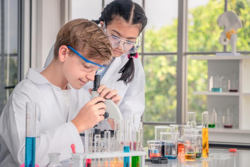 Studenti che utilizzano microscopio nella classe del laboratorio di scienza fotografia stock libera da diritti