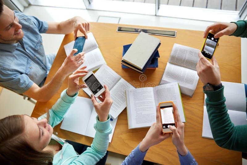 Studenti con gli smartphones che fanno gli strati di imbroglione immagine stock libera da diritti