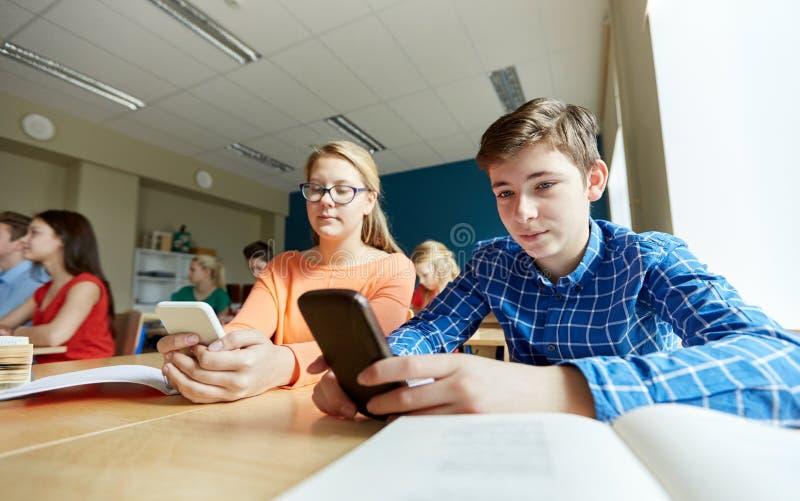 Studenti con lo smartphone che manda un sms alla scuola fotografie stock