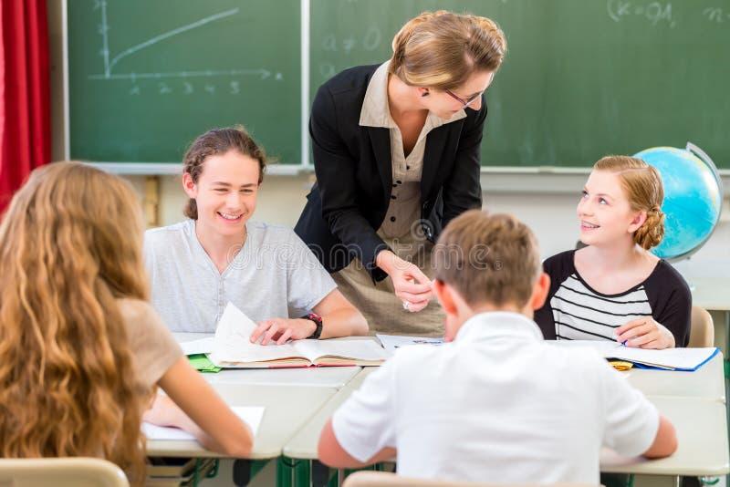 Studenti d'istruzione dell'insegnante lezioni di geografia a scuola fotografie stock