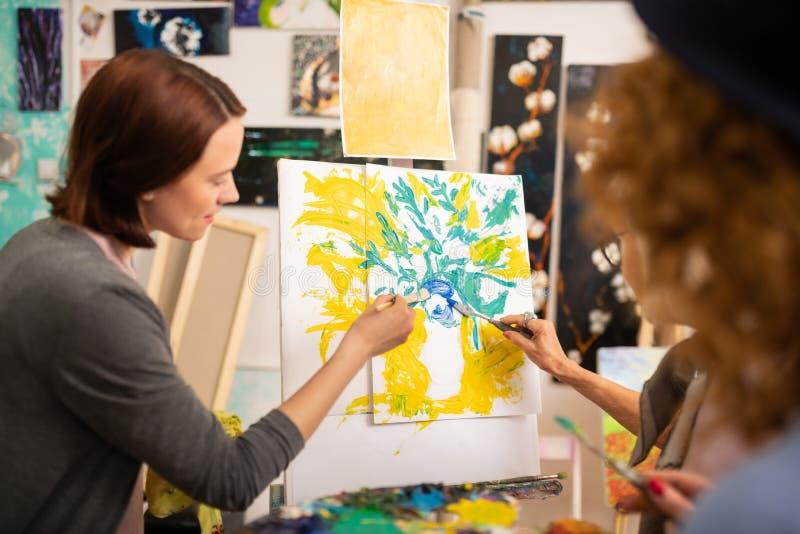 Studenti di arte che colorano insieme natura morta su tela immagine stock