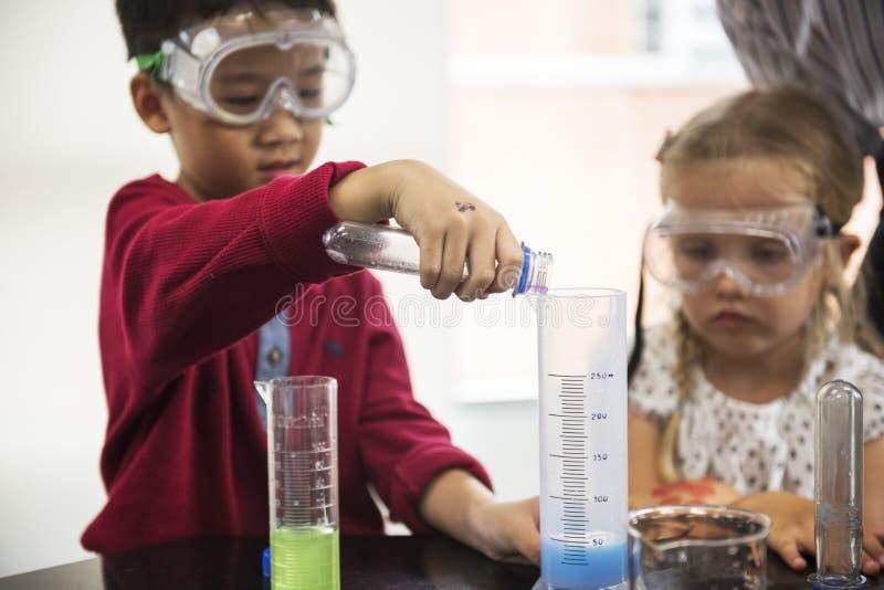 Studenti di asilo che mescolano soluzione nell'esperimento Labo di scienza fotografia stock libera da diritti