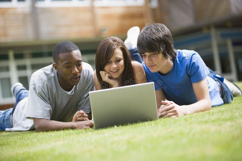 Studenti di college che per mezzo del computer portatile sul prato inglese della città universitaria, fotografie stock libere da diritti