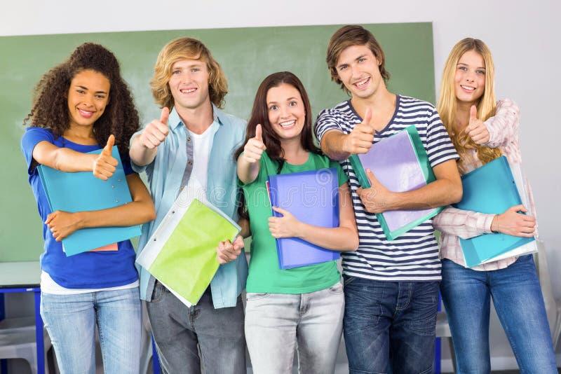 Studenti di college felici che gesturing i pollici su immagini stock libere da diritti